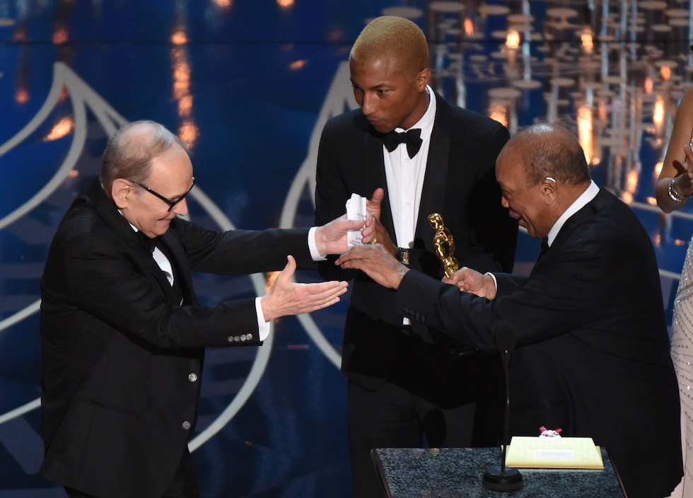 Ennio Morricone (L) accepts the award for Best Original Score, The Hateful Eight, from producer Quincy Jones (R) and Singer Pharrell Williams on stage at the 88th Oscars on February 28, 2016 in Hollywood, California. AFP PHOTO / MARK RALSTON / AFP / MARK RALSTON (Photo credit should read MARK RALSTON/AFP/Getty Images)
